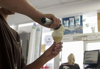 "Employee Shelby Susnick scoops some vanilla ice cream into a cone for one of her customers, while fellow employee Kari Bland takes orders. ""They started [making vegan ice cream] when I first started working here,""said Susnick.""A lot of costomers can't eat dairy."""